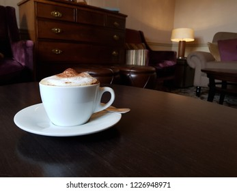 capuchino with chocolate on top on a table and furniture background in London.