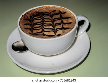 Capuchino cup of coffe with pattern on top of it
