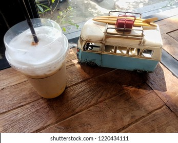 Capuchino ice coffee with model Van on wooden table