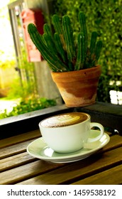 Capucino art coffee white cups and cantus pot on wood table backgrounds