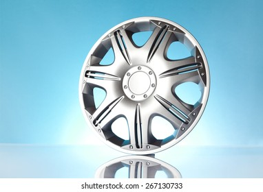 Car accessories - isolated car hubcap on blue background