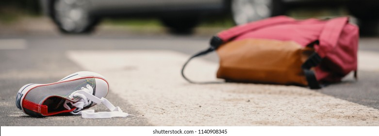 Car accident concept - an empty crosswalk with a child's shoe and backpack lying on the road and a vehicle in the background
