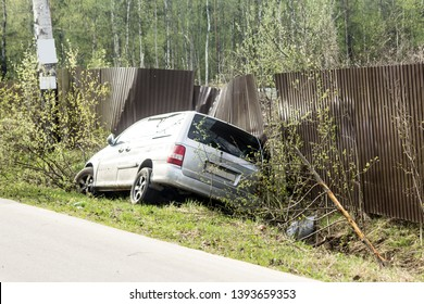 Car accident on a country road. The car is broken in front, slid into a ditch and damaged a metal fence.