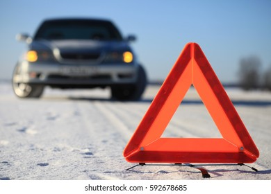 Car accident on winter road. Warning triangle.