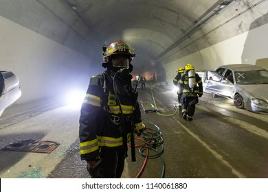 Car accident scene inside a tunnel, firefighters rescuing people from cars