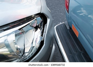 Car accident. Silver car collided with a blue pickup truck. Make the headlights break. Damaged chassis. On the main street in the city