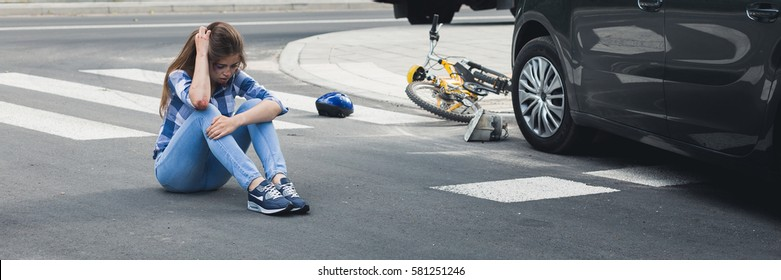 Car accident victim sitting on a street holding hand on her head, panorama