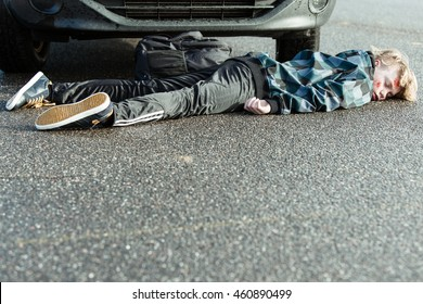 Car Accident - Young Teenage Boy Has Been Hit by Car and is Lying Injured, Unconscious or Dead on Pavement in front of Tires of Car, with Foreground Copy Space