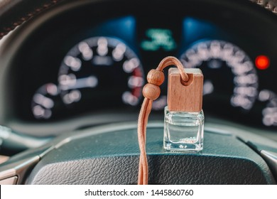 Car air perfume freshener bottle inside the car on the steering wheele. Aromatic liquid in the small bottle. Blurred dashboard lights in the background.