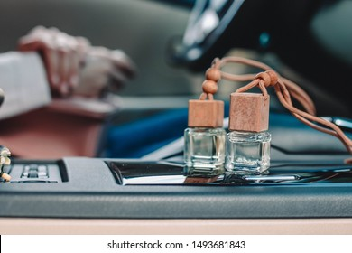 Car air perfume freshener bottles inside the car on car panel. Aromatic liquid in the small bottle. Female driver on blurry background