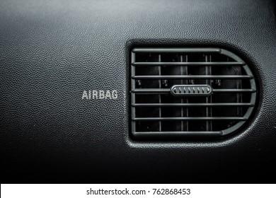 Car air ventilation. Airbag text next to it. Dark car itnerior background