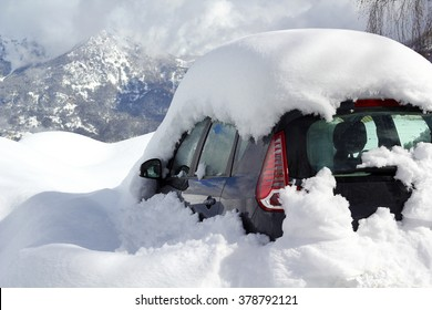 Car almost totally buried under a snow after a blizzard during the night at the alpin ski station