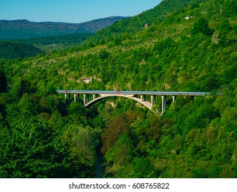 Car arched bridge in the forest, in the mountains. In Croatia, not far from the Plitvice Lakes.