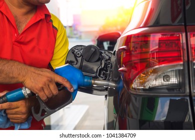 Car attendant holding fuel pump and refueling car at gas station