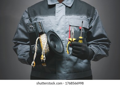 Car audio specialist holding in hands a car audio equipment on dark background.