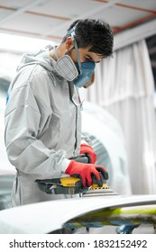 car, auto detailing. young auto mechanic man work with the use of orbital polisher, in auto repair shop, wearing uniform, protective mask and gloves