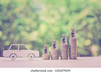 Car or auto loan, cash repayment, financial concept : White model sedan car and rows of rising coins with dollar bags, depicts saving money to buy a new car, or making down payment for second hand car