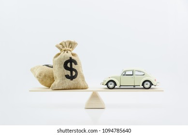 Car / Auto loan or transforming assets into cash concept : Car model, US dollar notes in jute bags on simple balance scale, depicts car owner or borrower turns personal properties into cash or wealth.