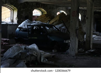 Car automobile scrapped salvaged stolen abandoned forgotten in derelict concrete building red black grey dark destroyed