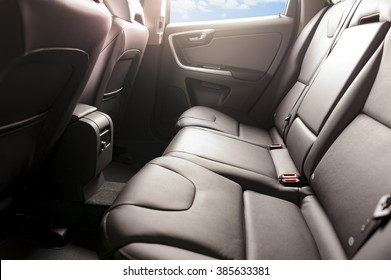 Car backseats with sun light flare and blue sky in the side windows