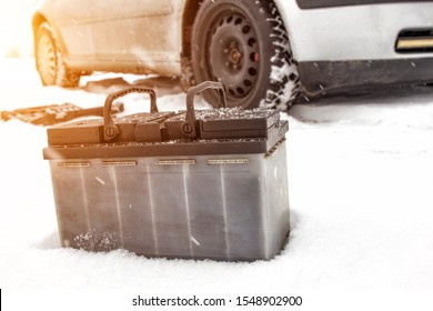 Car battery against the background of a car in winter. Winter battery discharge concept, copy space