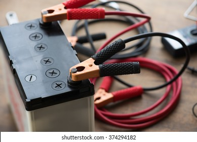 A Car battery with red and black battery Jumper Cables with copper clamps attached to the terminals. Automotive battery on a work desk with tools in background.
