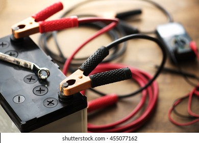 A Car battery with red and black battery Jumper Cables with copper clamps attached to the terminals.