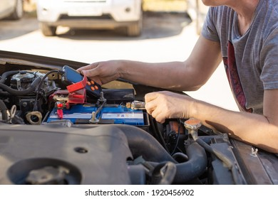 Car battery repair and inspection. The man measures the voltage and capacity of the battery with a tester. Car service.