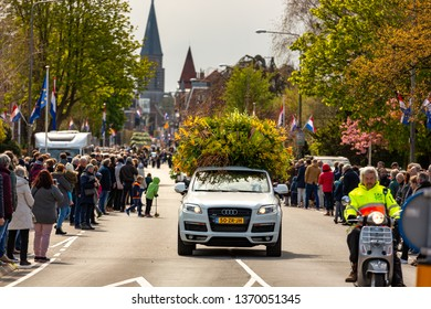 A car with beautiful flowers and lots of spectators at the annual bloemencorso bulb flower parade in the Hoofdstraat in the dutch village of Sassenheim. On saturday 13 april 2019.