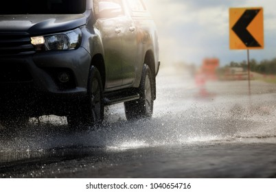 Car with big puddle of water spray from the wheels  through flood water after hard rain.Stop action ( capture with the high speed shutter) and selective focus,color toned.