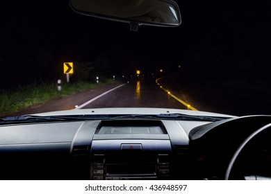 In the car, blur image of the road in the rain forest at dark night as background.