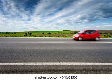 Car in blurred motion on country road. Side view. Rural landscape in summer day
