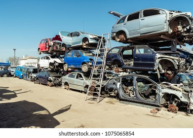 Car bodies waiting recycling/Piles of used cars disassembled in a cemetery yard car recycling center with a ladder and car shadows .