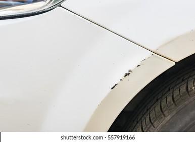 Car body damage, white front bumper fender, paint scratch.