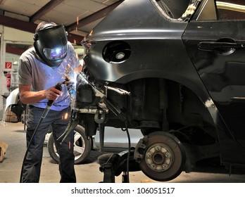 Car body worker welding car body.