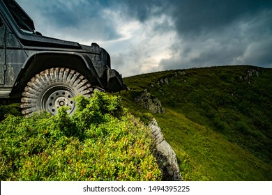 Car brakes with absorbers. Car tire. Tire for offroad. Truck car wheel on offroad steppe adventure trail. Wheel close up in a countryside landscape with a muddy road