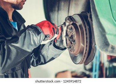 Car Brakes Servicing by Caucasian Vehicle Mechanic in His 30s. Automotive Industry.