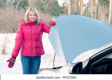Car breakage: young woman standing by the car with opened bonnet