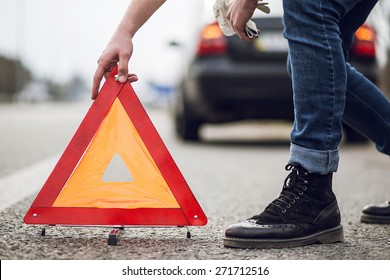 A car with a breakdown alongside the road, man sets the warning triangle