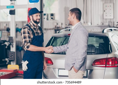 Car breakdown, check condition, inspection, engineering, insurance, repair concept. Side profile shot of satisfied businessman in classy suit shaking arm of mechanic, near his property, silver car