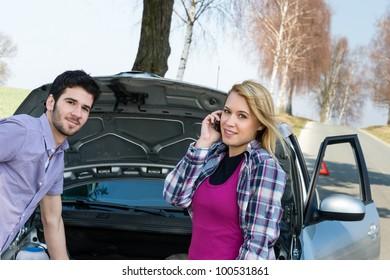 Car breakdown couple calling for road assistance repair motor defect