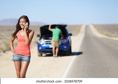 Car breakdown - woman phone calling auto service. Positive happy smiling woman on smart mobile phone, with man looking at car engine in background on highway in California, USA.