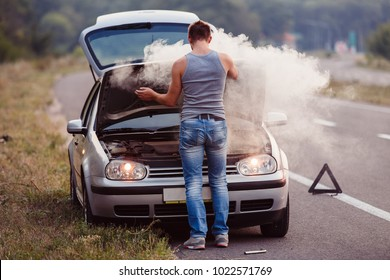 The car broke down, smokes from under the hood, the driver shocked