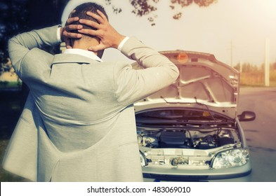 Car broke. Man looking at the broken car not knowing what to do. Car service. Tow service. Car breakdown.