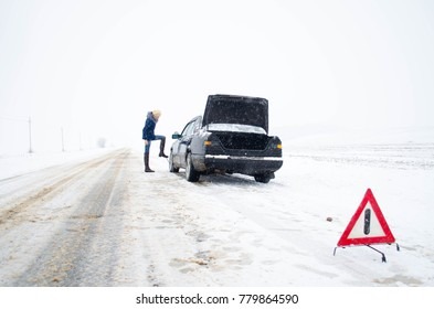 car broke, need to put the spare tire, an emergency on the road in winter, dangerous winter road covered with snow