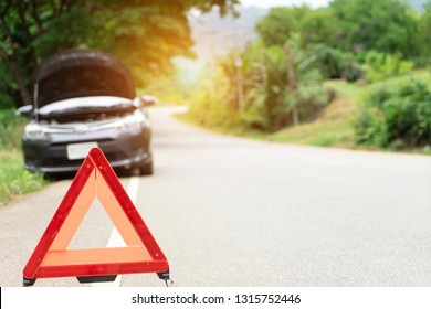 car broken down on road with emergency help sign. car break down damage trouble on country mountain road, traffic warning red triangle sign on asphalt nature road. Emergency stop concept.