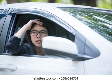 The car is broken and parked on the side of the road, the stressful young woman is calling the car mechanic with a mobile phone.