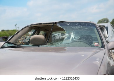 Car with a broken windhield lies abandoned with the rubber sealing falling into the hole of the window