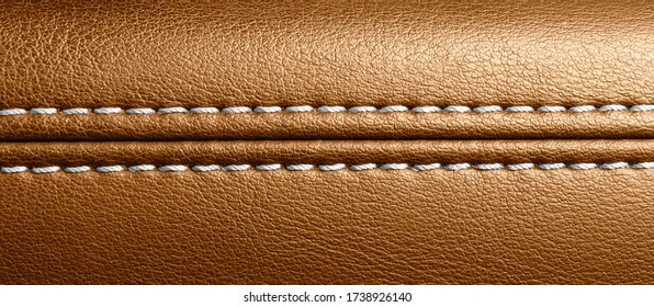 Car brown leather interior. Part of perforated leather door handle details. Orange Perforated leather texture background. Texture, artificial leather with stitching.