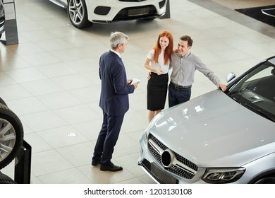 Car Business, Car Dealership, Customers and Rep Concept. Top view of salesman talking to a young couple at the dealership showroom.